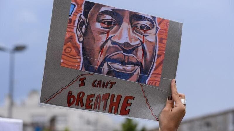 "A woman holds a placard depicting George Floyd's face and reading ""I can't breathe"" in Bordeaux, on June 9, 2020. (AFP)"