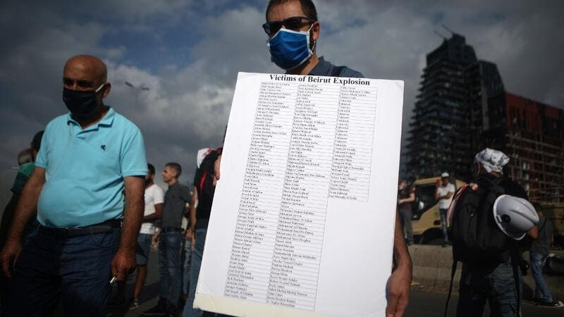 A Lebanese man carries a placard bearing the names of the Beirut port explosion, during a commemoration ceremony across from the capital's harbour, on August 11, 2020. PATRICK BAZ / AFP