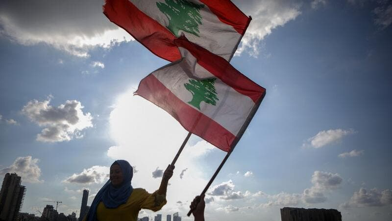 Lebanese women wave the national flag during a commemoration ceremony for the victims of the Beirut port explosion across from the capital's harbour, on August 11, 2020. PATRICK BAZ / AFP