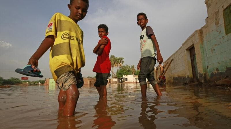 Sudanese boys make their way through a flooded street at the area of al-Qamayir in the capital's twin city of Omdurman, on August 26, 2020. Sudan on September 5 declared the imposition of a three-month state of emergency nationwide after record-breaking torrential floods caused by more than a month heavy rains left dozens dead and 100,000 damaged properties in their wake, in one of the worst natural disasters in decades, according to state news agency SUNA. ASHRAF SHAZLY / AFP