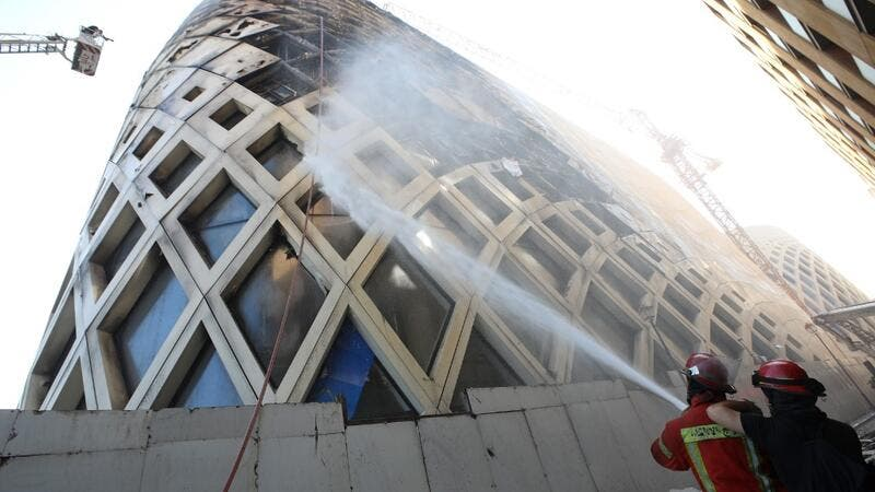 Lebanese firefighters douse the flames of a blaze that engulfed a landmark modern building, designed by the late world-renowned British-Iraqi architect Zaha Hadid, in central Beirut on September 15, 2020 The reasons behind the fire, which comes one week after another one at a Beirut port warehouse containing food, were not immediately known. ANWAR AMRO / AFP