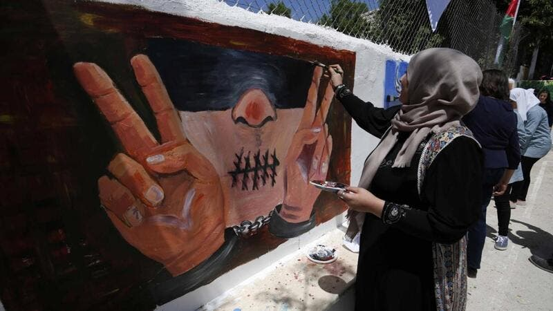 Palestinian women paint murals as they mark Palestinian Prisoner Day in the West Bank city of Ramallah on 17 April 2016 (AFP)