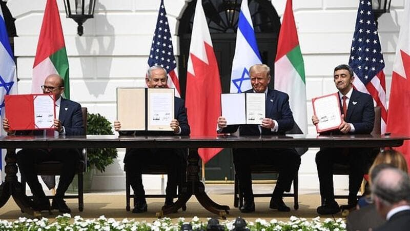 The four leaders hold up the signed copies of the Abraham Accords - they signed one in English, one in Hebrew and two in Arabic (AFP)