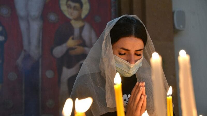 An Armenian woman, wearing a face mask, prays in a church in Yerevan on October 17, 2020, for Armenians killed during fighting over the breakaway region of Nagorno-Karabakh. Karen MINASYAN / AFP