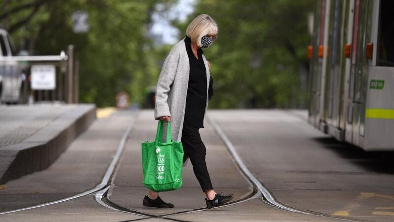A woman crosses a street in Melbourne on October 18, 2020, as the state government announces a lifting of some restrictions as the city battles a second wave of the Covid-19 coronavirus. William WEST / AFP