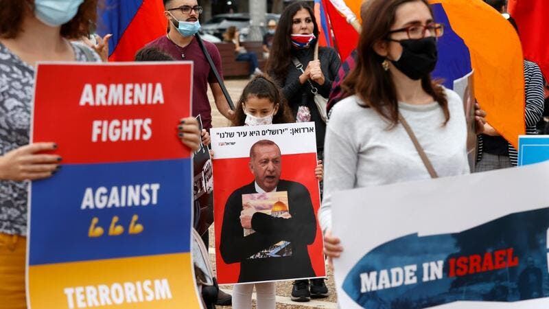 Members of the Armenian community in Israel hold banners in the coastal city of Tel Aviv on November 6, 2020, as they protest against Israel's arms sales to Azerbaijan and Turkey's support to the latter. JACK GUEZ / AFP