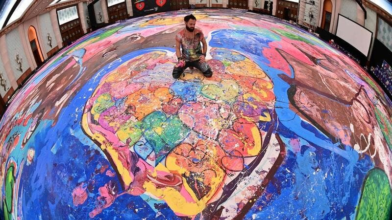 A picture taken with fisheye lens shows contemporary British artist Sacha Jafri sitting on his record-breaking painting entitled 'The Journey of Humanity'. AFP