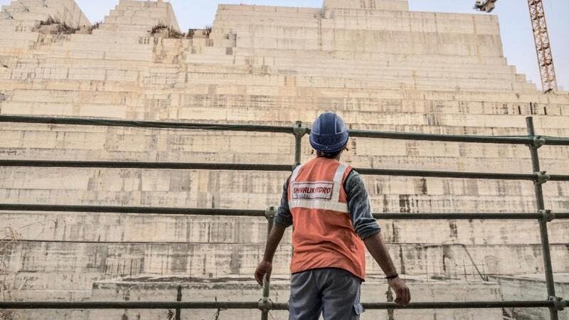 Construction worker eyes progress on the Grand Ethiopian Renaissance Dam in Ethiopia last December (AFP)