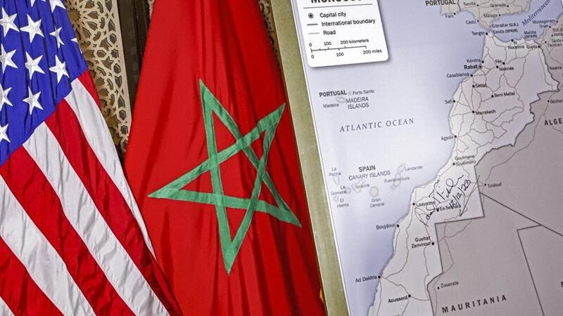 This file photo taken on December 12, 2020 shows (L to R) US and Moroccan flags next to a US State Department-authorised map of Morocco recognising the internationally-disputed territory of the Western Sahara (bearing a signature by US Ambassador to Morocco David T. Fischer) as a part of the North African kingdom, in Morocco's capital Rabat. US President Donald Trump's surprise backing of Morocco's claim to sovereignty over disputed Western Sahara upended years of international consensus, but will this brea
