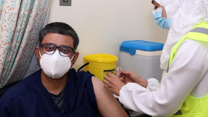 A doctor receives his first dose of the Pfizer-BioNTech COVID-19 vaccine in the Omani capital Muscat on December 27, 2020. MOHAMMED MAHJOUB / AFP