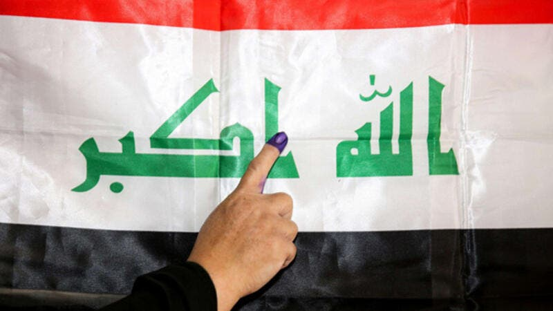 An Iraqi woman voter her ink-stained index finger before a national flag after having cast her vote in the first parliamentary election in Baghdad, May 12, 2018. (AFP)