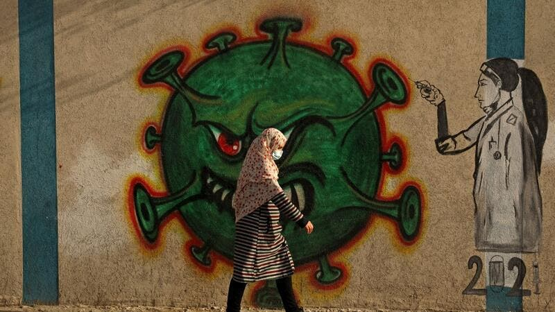 A Palestinian woman, wearing a protective mask amid the COVID-19 pandemic, walks past a coronavirus-inspired mural in Gaza City, on February 2, 2021. Mohammed ABED / AFP