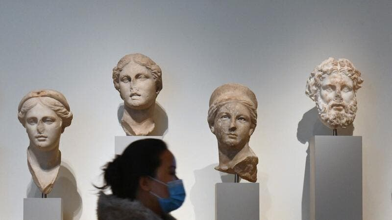 A visitor wearing a facemask walks past stone sculptures at The Metropolitan Museum of Art, 'The Met' in New York City on February 9, 2021. Angela Weiss / AFP