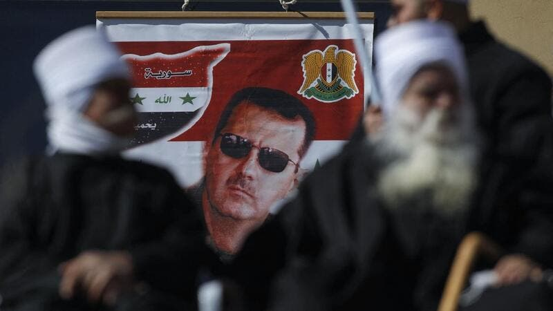Members of the Druze community sit near a billboard bearing the portrait of Syrian President Bashar Assad during a rally in the village of Majdal Shams in the Israeli-annexed Golan Heights on February 14, 2021, to protest the 1981 Israeli annexation law of the strategic plateau which the Jewish state captured from Syria during the 1967 Arab-Israeli war. JALAA MAREY / AFP