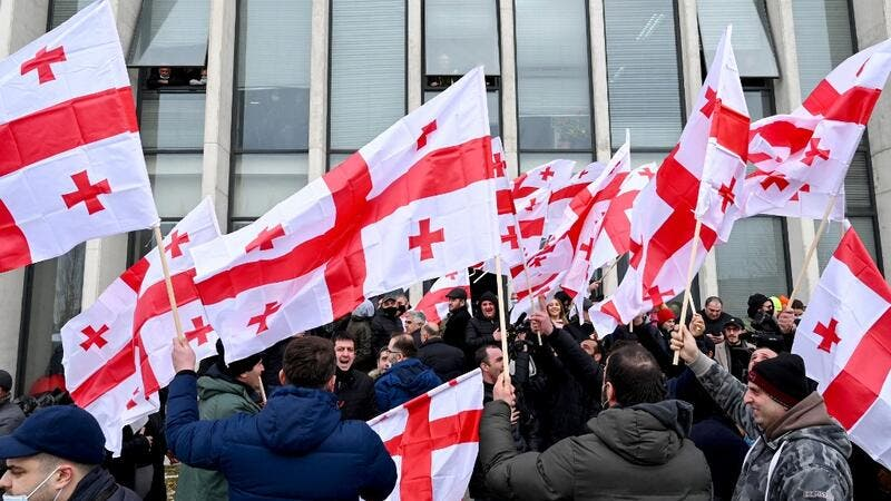 Georgian opposition supporters wave national flags reacting on the announcement of Prime Minister Giorgi Gakharia's resignation in front of the United National Movement (UNM) headquarters in Tbilisi on February 18, 2021. Vano Shlamov / AFP