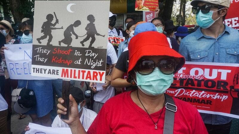 Protesters hold signs as they take part in a demonstration against the military coup in front of the Indonesian embassy in Yangon on February 23, 2021. Sai Aung Main / AFP