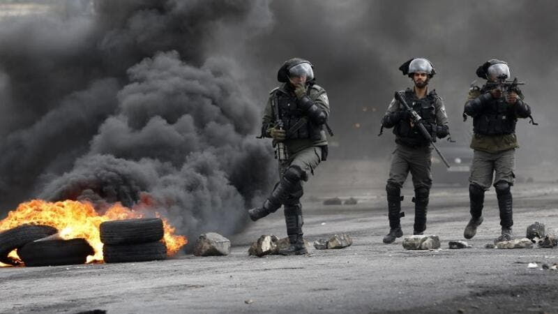 Israeli border guards walk through fumes from burning tires during clashes with Palestinian protesters near the Israeli settlement of Beit El in the Israeli occupied West Bank, on Mar. 30, 2018, after Land Day demonstrations. Land Day marks the killing of six Arab Israelis during 1976 demonstrations against Israeli confiscations of Arab land.