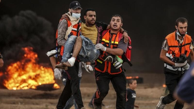 Palestinian paramedics carry away a protester who was injured during clashes following a demonstration near the border with Israel east of Gaza City on October 26, 2018. (MAHMUD HAMS / AFP)