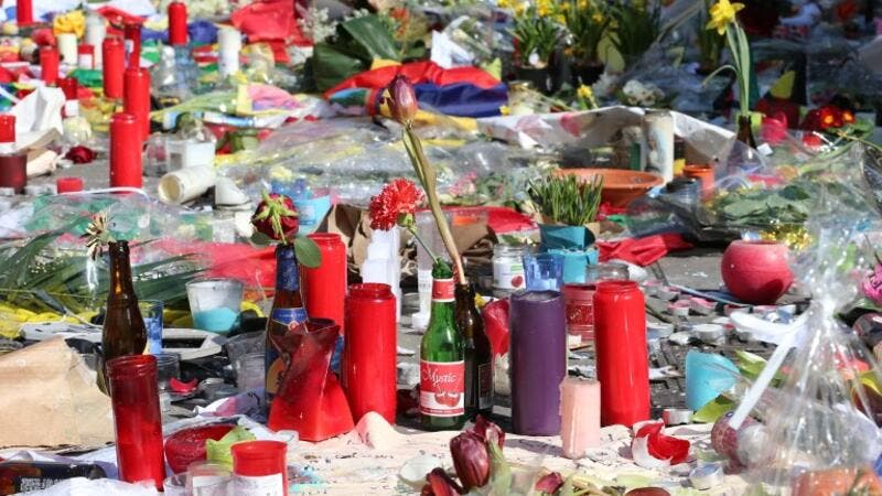 Flowers and candles are laid in a makeshift memorial on the Place de la Bourse (Beursplein) in central Brussels, on March 27, 2016, in tribute to the victims of the coordinated terror attacks in the city claimed by Daesh on March 22, in which 31 people were killed and over 300 injured. (AFP/Nicolas Maeterlinck)