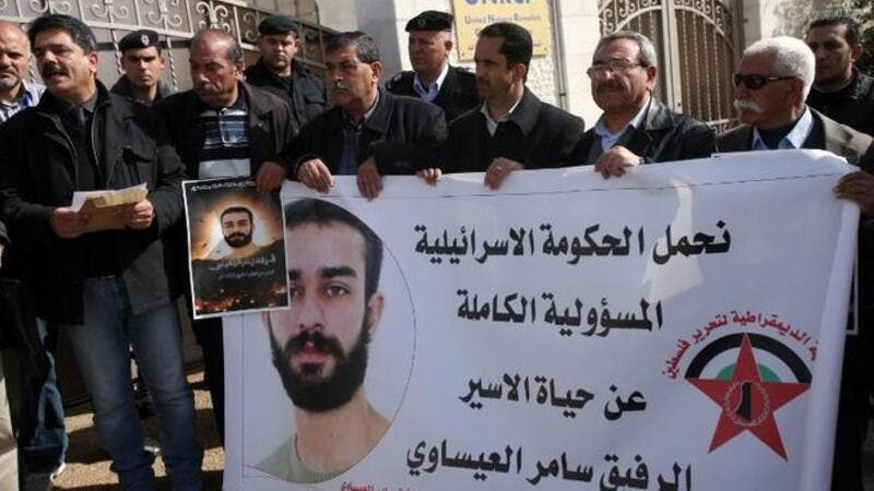 Palestinian protesters hold placards during a demonstration in Ramallah in support with Palestinian prisoners held in Israeli jails, some of whom are observing a hunger strike. (AFP PHOTO/ABBAS MOMANI)