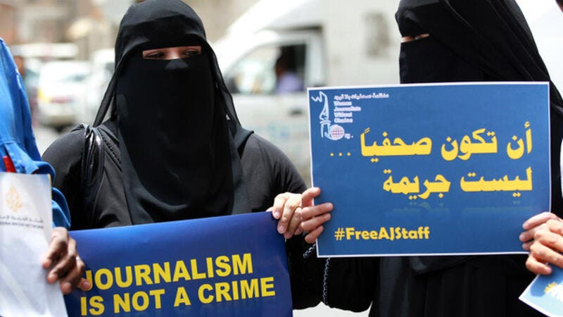 Yemeni women hold placards during a protest on 25 June 2014 in the capital Sanaa in solidarity with Al Jazeera journalists jailed in Egypt at the time. (AFP/File)