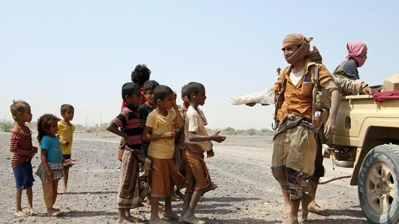 Pro-government fighters give food to Yemeni children on the road leading to the southwestern port city of Mokha on January 26, 2017. Saleh Al Obeidi (AFP)