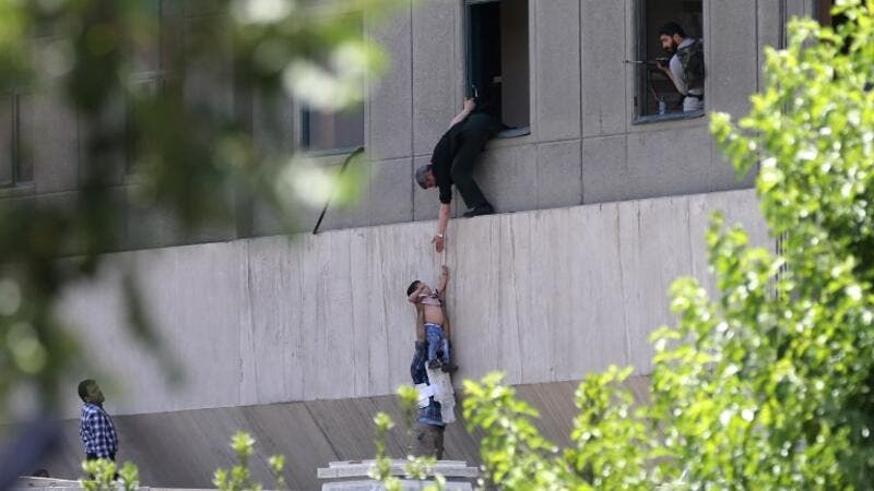 Iranian policemen evacuate a child from the parliament building in Tehran on June 7, 2017 during an attack on the complex. (Omid Vahabzadeh/Fars News/AFP)