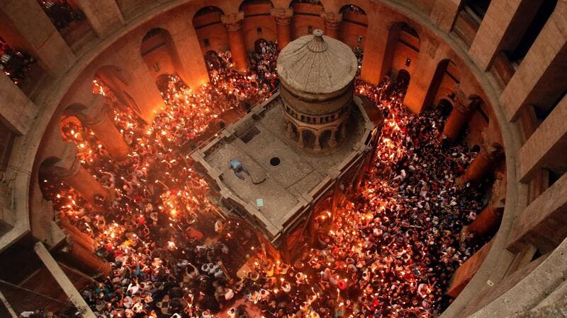 "Christian Orthodox worshippers hold up candles lit from the ""Holy Fire"" as thousands gather in the Church of the Holy Sepulchre in Jerusalem's Old City. (AFP/ File Photo)"
