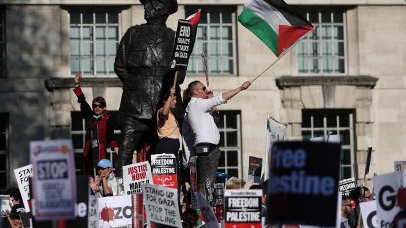 Pro-Palestine demonstrators hold placards and wave flags during a protest opposite the entrance to Downing Street in central London /AFP