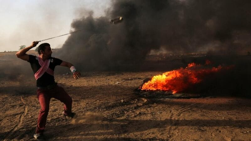 A Palestinian demonstrator uses a slingshot during clashes with Israeli forces along the border with the Gaza strip (AFP/File Photo)