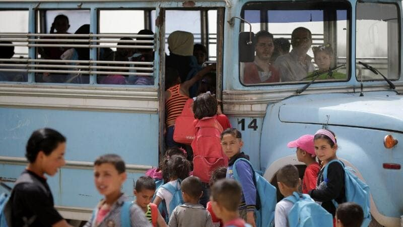 Syrian refugee children prepare to board a school bus at an unofficial refugee camp in Lebanon's town of Bar Elias in the Bekaa Valley on May 13, 2016. (AFP/Joseph Eid)