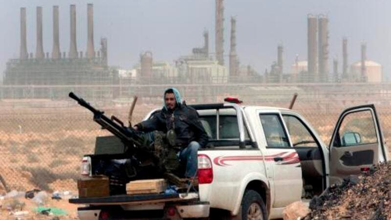 Libyan rebels sit with an anti aircraft weapon in front of an oil refinery. (AFP/File)