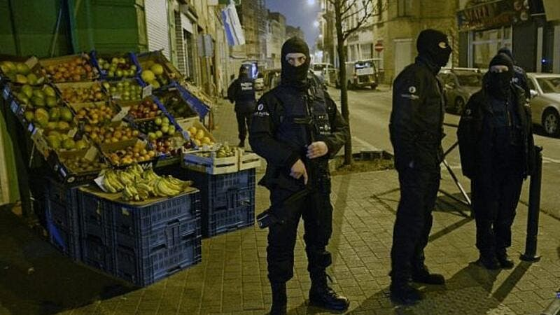 Police stand guard near a scene of a police operation in the Molenbeek-Saint-Jean district in Brussels, on March 18, 2016, as part of the investigation into the Paris November attacks (AFP)
