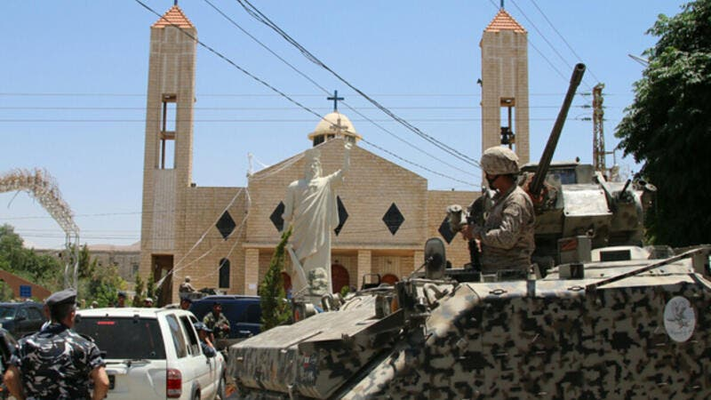 Lebanese soldiers stand guard in front of a church where a suicide bomber blew himself up the previous day in the Christian village of al-Qaa. (AFP/File)