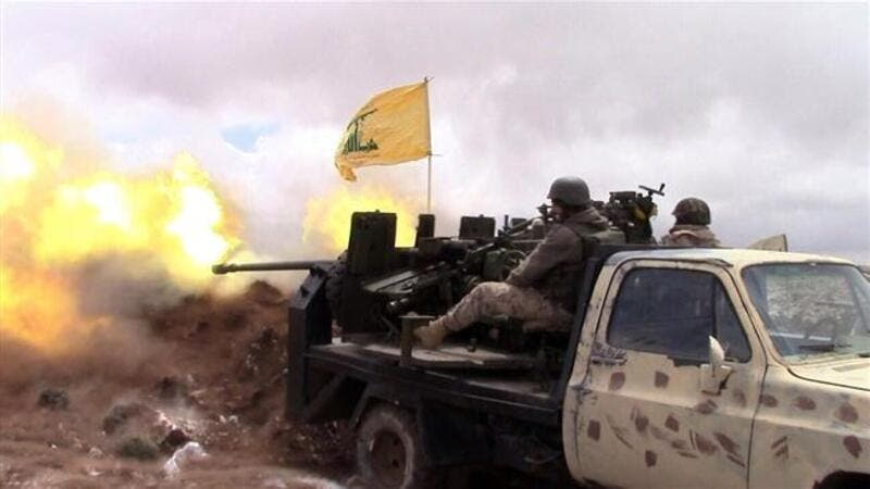 A handout picture released by the Hezbollah press office on May 16, 2015, shows a Hezbollah fighter firing towards militants on the Syrian side of the Qalamoun hills close to the Lebanese border. (AFP/File)