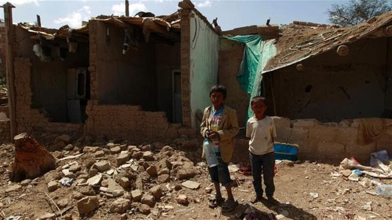 Yemeni children stand outside houses which were destroyed several months ago in an airstrike by Saudi warplanes at a slum in Sana'a, March 12, 2016. (AFP/File)