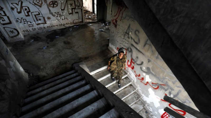 A female fighter from the Kurdish People's Protection Units (YPG) descends stairs in an abandoned building in Raqa's eastern al-Sanaa neighbourhood, on the edge of the old city, on August 13, 2017 / AFP