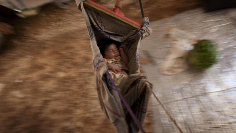 A Syrian refugee baby sleeps in a hammock at the Bab al-Salam refugee camp in Syria's northern city of Azaz on July 15, 2013. (Source: AFP/JM LOPEZ)
