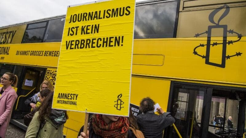 "Placard reads ""journalism is not a crime"" at concert in Berlin on International Press Freedom Day (John Macdougall/AFP)"
