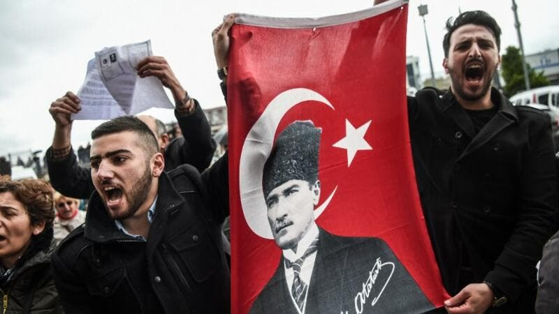 "Supporters of the ""No voters"" and members of Turkey's main opposition party, the Republican People's Party (CHP), hold a flag of Mustafa Kemal Ataturk, founder of modern Turkey as they gather at the Caglayan courthourse to submit their petition to object alleged irregularities in Turkish vote on April 18, 2017 in Istanbul. (AFP/Ozan Kose)"