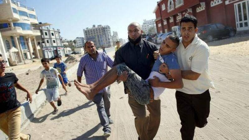 A Palestinian carries a wounded boy following an Israeli military strike (AFP/File Photo)