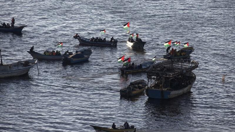 Palestinians sail boats bearing their national flag in the port of Gaza City in support of the Gaza-bound flotilla of international female activists attempting to break the Israeli blockade on the Hamas-run Gaza Strip on October 5, 2016. (AFP/Mahmud Hams)
