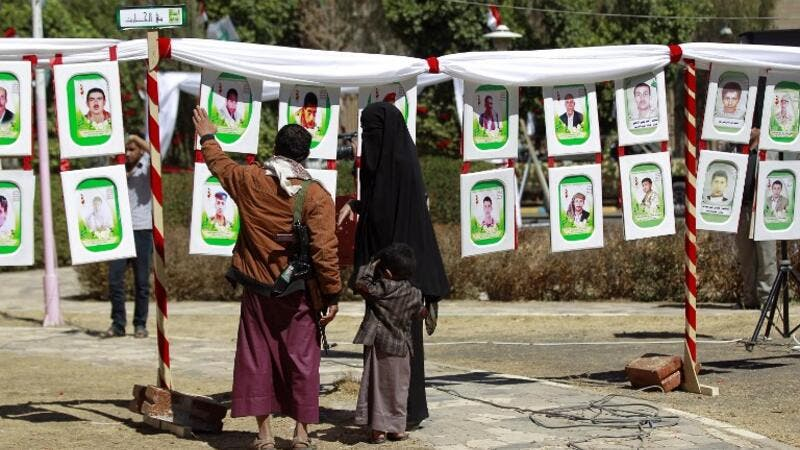 "Yemenis look at portraits of Shiite Huthi rebels, reportedly killed in fighting against Saudi-backed Yemeni forces, displayed during an exhibition marking their ""Martyrs' Day"" on February 27, 2016 in the capital Sanaa. (AFP/Mohammed Huwais)"