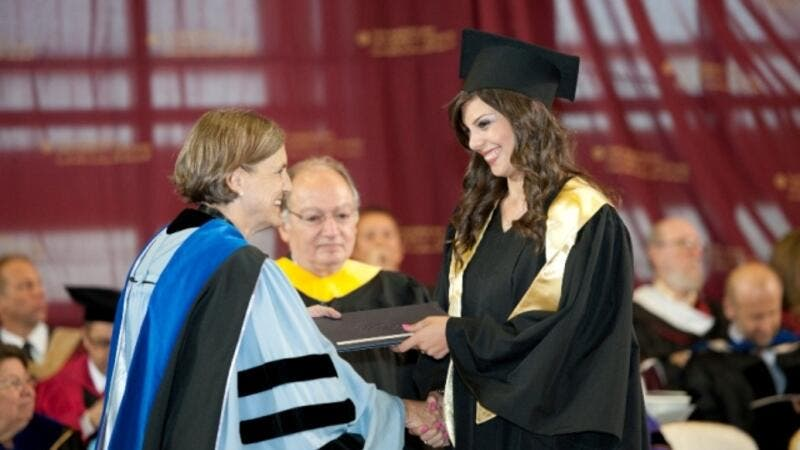 AUC undergraduate student receiving her degree from AUC President