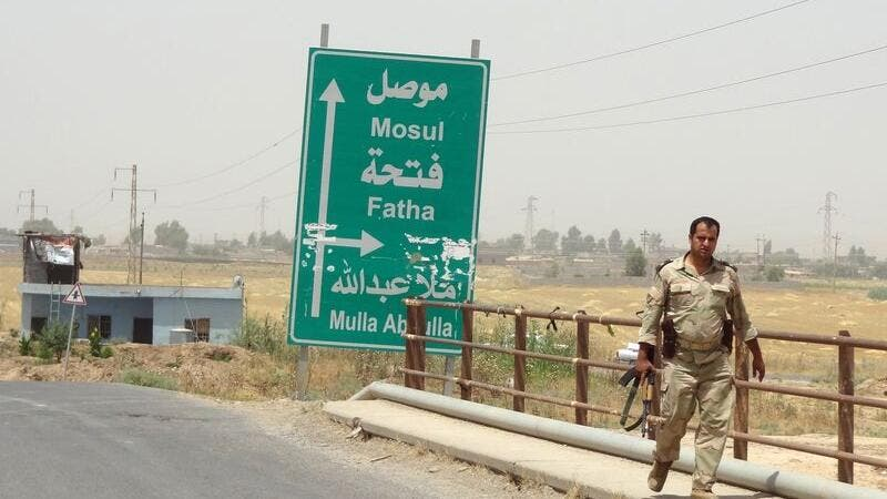An Iraqi solider walks past a sign pointing toward Mosul. (AFP/File)