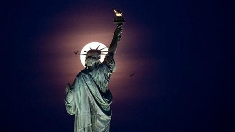 Full moon rises behind the Statue of Liberty in New York City, 2019 /AFP