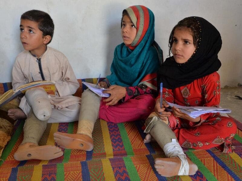 In this photograph taken on May 14, 2019, Hamisha Gul's grandchildren, who lost their legs following unexploded rocket explosion, attend and study at a class in their house in Khogyani district of Nangarhar province. NOORULLAH SHIRZADA / AFP
