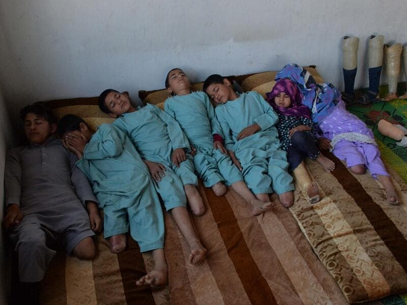 In this photograph taken on May 3, 2019, Hamisha Gul's sons and grandchildren, who lost their legs following unexploded rocket explosion, rest in their bedroom in Khogyani district of Nangarhar province. NOORULLAH SHIRZADA / AFP