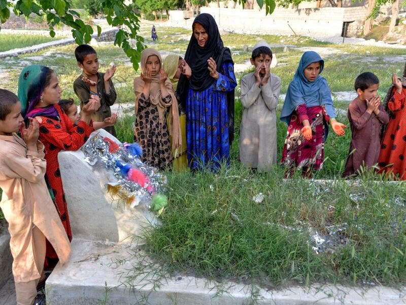 In this photograph taken on April 22, 2019, Afghan woman Niaz Bibi (C in blue), 70, and her orphaned grandchildren pray on the tombs of her sons and grandsons killed by ISIS militants in the Kot district of the Nangarhar province. NOORULLAH SHIRZADA / AFP