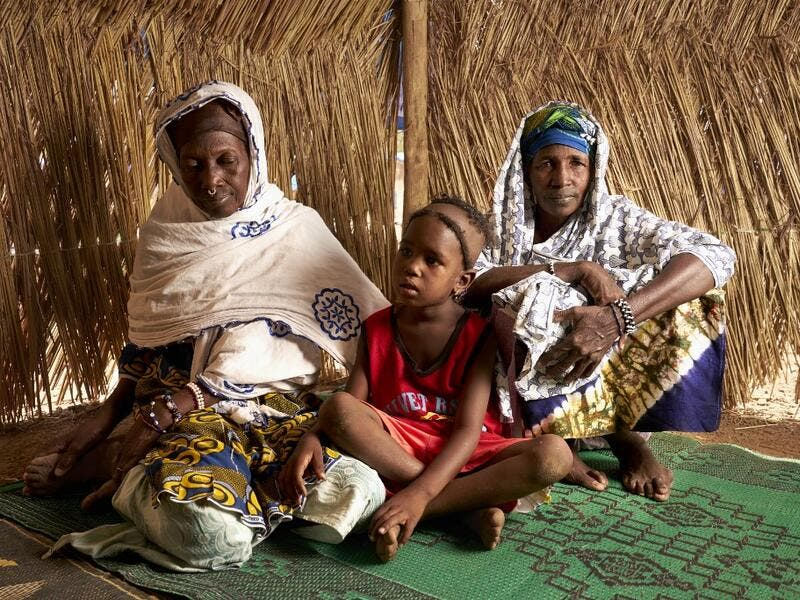 Dicko Sidibe (R) poses with her daughter and her sister Soutra (L) in a refugee camp on May, 13, 3019 in Bamako. After receiving several threats and attacks against their village in the province of Bankass, they fled central Mali to find a safe place in Bamako. (MICHELE CATTANI / AFP)